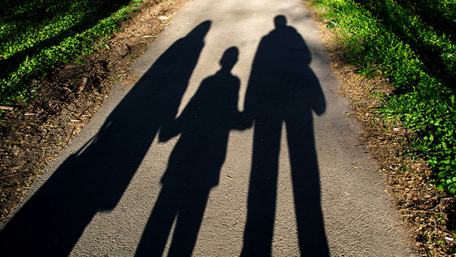shadows of parents and child across paved road