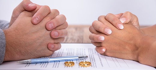 zoomed in image of two sets of hands clasped together over a divorce mediation documen