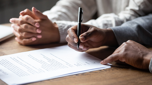 Close up view of mediator and client writing settlement agreement